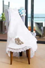 bridal dress, bouquet and shoes on a chair