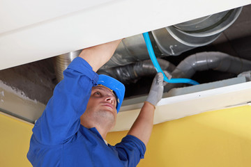 Worker holding blue pipe in place under air ducts