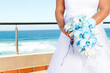 bride holding beautiful bouquet, background is sea view