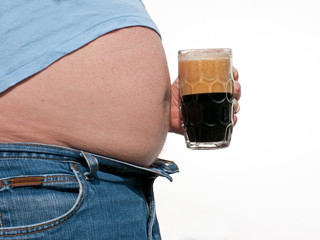 Man with big, fat beer belly, holding a glass of stout.