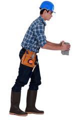 Builder carrying brick