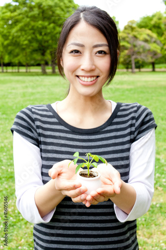 asian woman holding small plant in the park