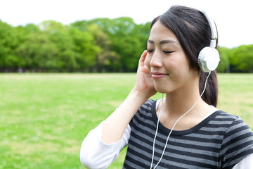 attractive asian woman listening to music in the park