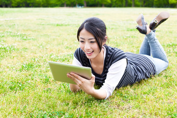 attractive asian woman using tablet computer in the park