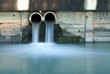 Leinwandbild Motiv Dirty drain polluting a river