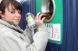 Woman putting glass in a recycling bin