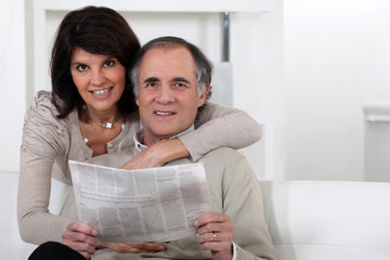 Mature couple looking at a newspaper