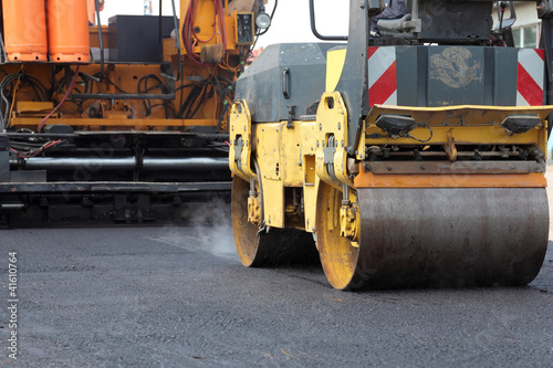 Roadwork road roller and paving machine at asphalt