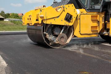 Roadwork road roller at hot asphalt