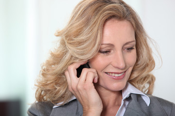 Blond businesswoman speaking on the phone