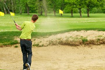 Junger Golfspieler beim Abschlag im Bunker