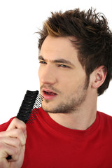 young man holding hairbrush as makeshift microphone
