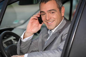 Businessman using a cellphone in his car