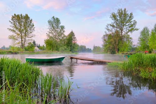 Rural landscape with boat and footbridge on the Narew river.