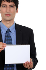 Businessman holding note pad