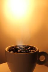 Dampfende Kaffeebohnen in Tasse