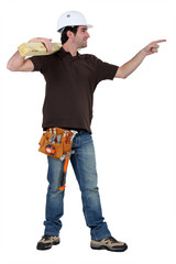 carpenter in profile holding lumber pointing at someone