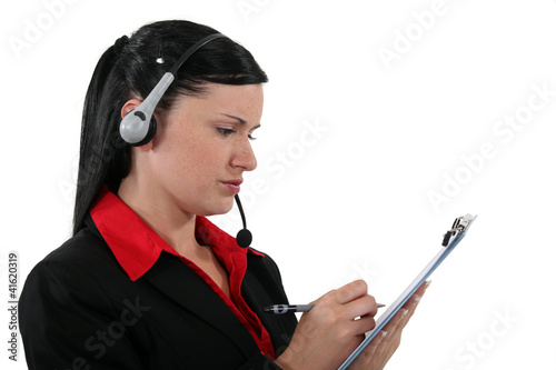 Office assistant writing on a clipboard