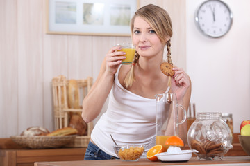 Blond woman drinking fruit juice and eating a biscuit