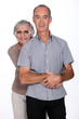 Affectionate senior couple stood in the studio
