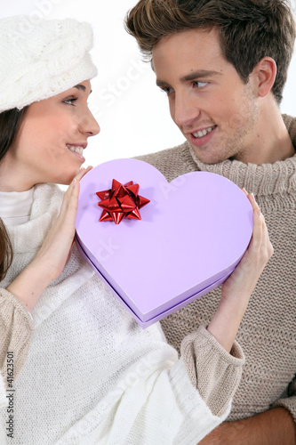 Couple holding heart-shaped box