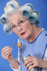 funny grandmother eating canned food with fork