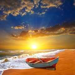 small boat on a sea coast at the sunset