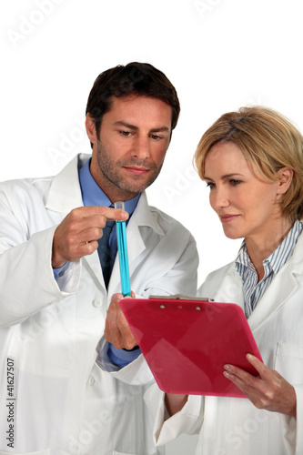 Couple of lab technicians examining test tube