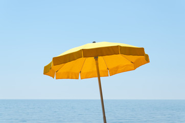 yellow umbrella over sea under blue sky