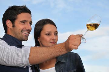 Couple tasting wine outdoors