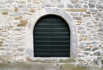 old dark green wooden door on stone wall