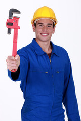 young workman in jumpsuit holding adjustable spanner