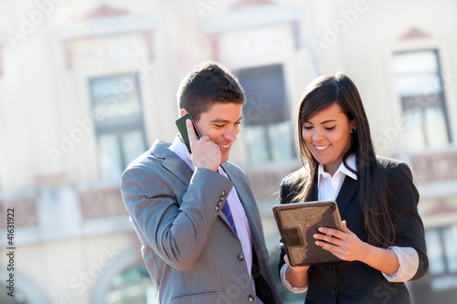 Business couple outdoors with tablet.