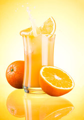 Splashing Fresh Orange Juice on yellow background