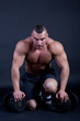 Strong man preparing to lift two heavy dumbbells
