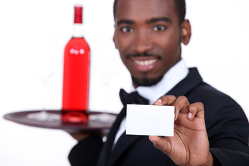 Waiter with a bottle of rose wine and a blank business card