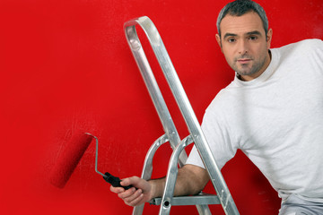 Man painting red wall with roller brush