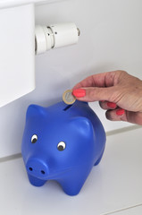 Frauenhand steckt 1 Euro in ein Sparschwein an einer Heizung