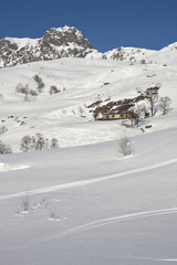 With snowy mountain huts in the Alps
