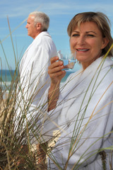 A mature couple down the beach in bathrobe.