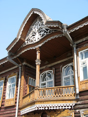 A fragment of a wooden house with a balcony thread