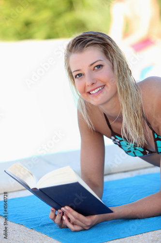 Young woman lounging around the pool