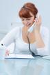 junge frau macht notizen beim telefonieren