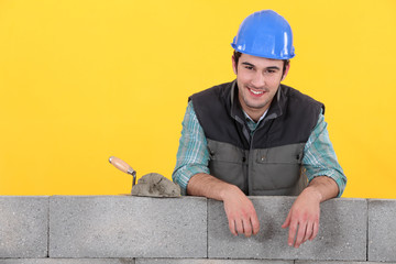 Cheerful mason stood by unfinished wall
