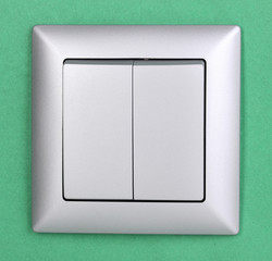 Modern light switch on green background