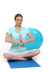 Woman sat in yoga position by exercise ball
