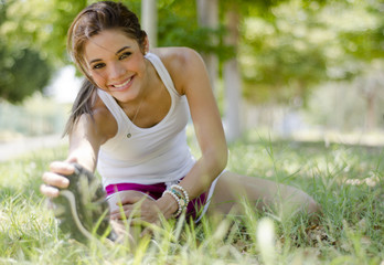 Cute girl stretching on the ground at the park