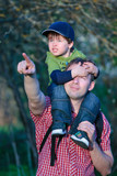 Cute little boy sitting on father's shoulders