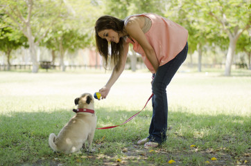 Cute woman playing with her dog at the park