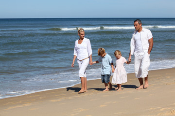 Family with children walking on the beach